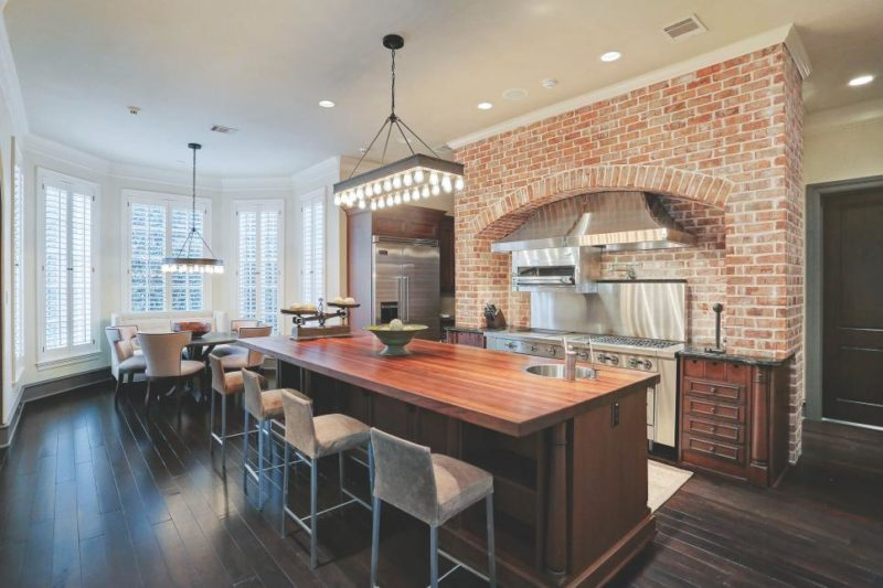 Chef Kitchen With Bar Stools and Brick Wall