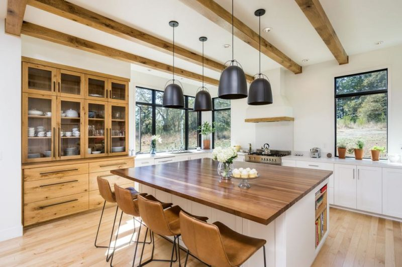 Large Kitchen Eat-In Island With Brown Leather Bar Chairs and Polished Wood Countertop Under Black Pendant Lights